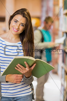 Two young students by bookshelf in the library