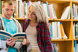 Students reading book against bookshelves in library