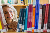 Smiling female student selecting book in the library