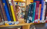 Smiling female student reading book in the library