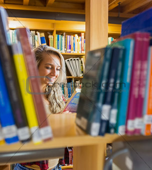 Student reading book amid bookshelves in the library