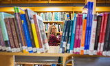 Smiling female amid bookshelves in the library