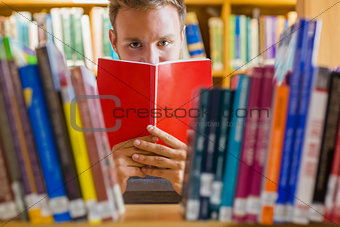 Male student holding book in front of his face in the library