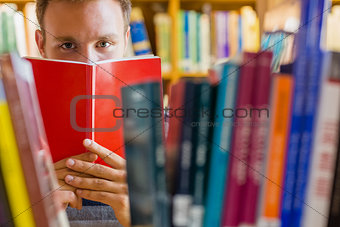 Student holding book in front of his face in the library