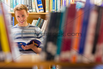 Male student reading a book in the library