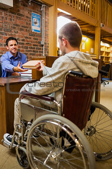 Student in wheelchair at the library counter