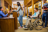 Students with handicapped man in row at library counter
