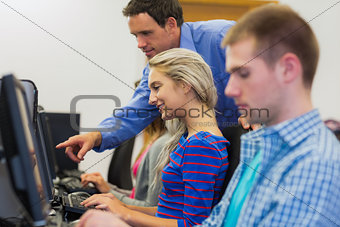 Teacher showing something on screen to student in computer room