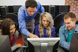Teacher showing something on screen to students in computer room