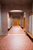 Empty brick walled corridor with tiled flooring in college