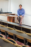 Mlegant male teacher sitting in the lecture hall
