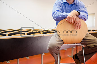 Mid section of a teacher on chair in lecture hall