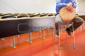 Low section of a teacher on chair in lecture hall