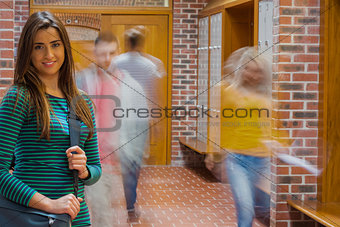 Smiling girl with blurred students walking through corridor