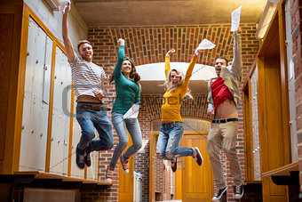 Students jumping in college corridor