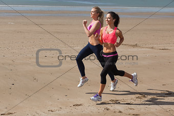 Full length of healthy women jogging on beach