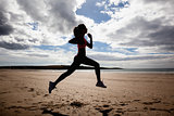 Full length of silhouette healthy woman jogging on beach