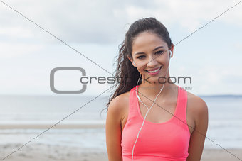 Smiling healthy with earphones on beach
