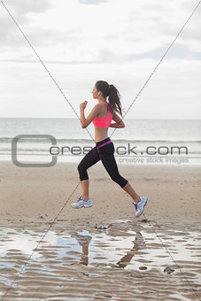 Full length of a healthy woman jogging on beach