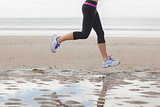 Low section of healthy woman jogging on beach