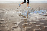 Low section of a healthy woman jogging on beach