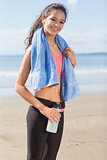 Beautiful smiling healthy woman with water bottle on beach