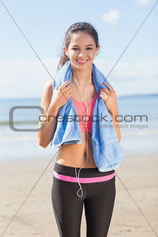 Beautiful healthy woman with towel around neck on beach