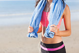 Mid section of healthy woman with towel around neck on beach