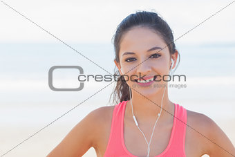 Close up of smiling healthy with earphones on beach