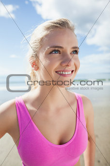 Smiling healthy woman in pink sports bra on beach