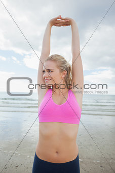 Smiling toned woman stretching hands on beach