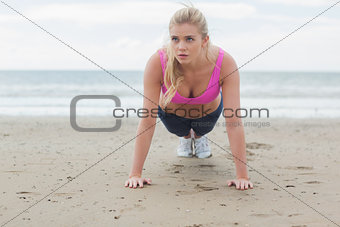 Beautiful woman doing push ups on beach