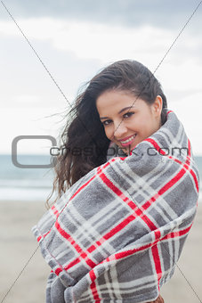 Portrait of woman covered with blanket at beach