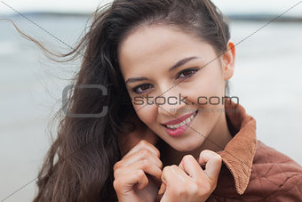 Cute smiling woman in stylish brown jacket on beach