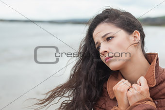 Cute thoughtful young woman on beach