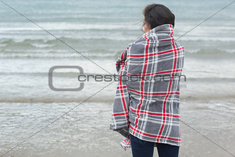 Rear view of woman covered with blanket looking at sea on beach