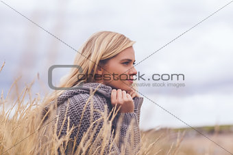Cute thoughtful young woman lying at beach