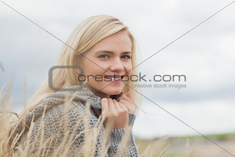 Close up side view portrait of a cute smiling young woman lying at beach