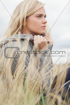 Side view of a cute thoughtful young woman lying at beach