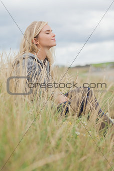 Side view of cute thoughtful woman sitting at beach