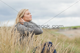 Side view of a cute thoughtful woman sitting at beach
