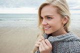 Cute smiling woman in gray knitted jacket on beach