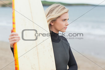 Beautiful young woman with surfboard on beach