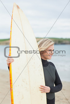 Smiling beautiful woman with surfboard on beach