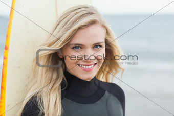 Portrait of a smiling beautiful woman with surfboard