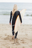Rear view of a woman in wet suit holding surfboard at beach