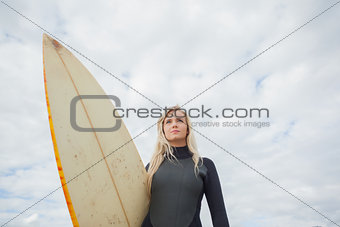 Beautiful woman with surfboard against cloudy sky