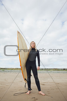 Beautiful woman in wet suit holding surfboard at beach