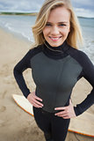 Beautiful young woman in wet suit at beach