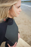 Side view of beautiful blond in wet suit at beach